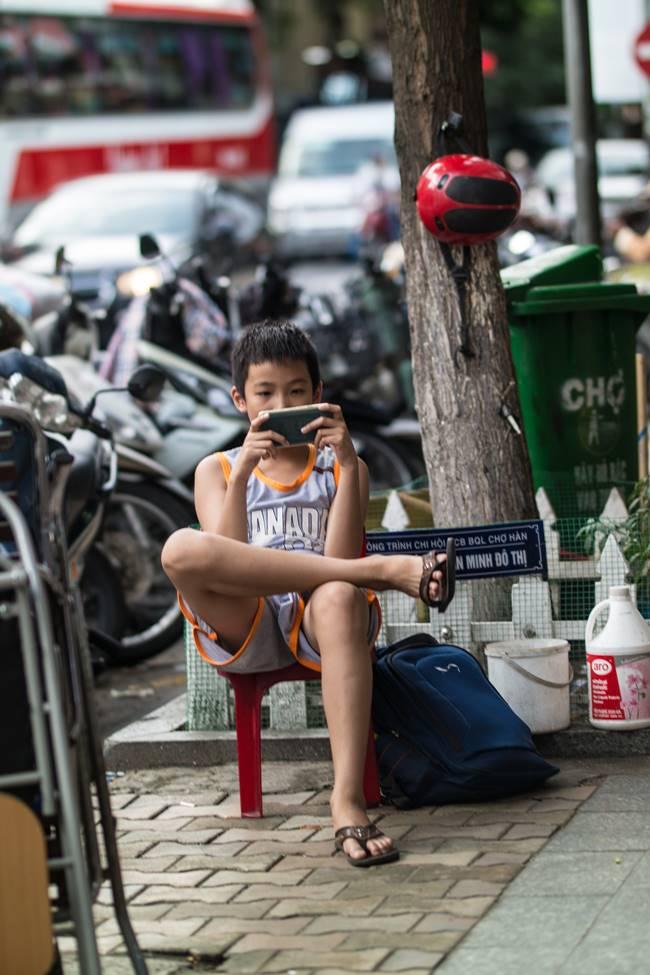 베트남 다낭 여행 - 다낭 한마켓 앞 스마트폰에 몰두하고 있는 아이-3717