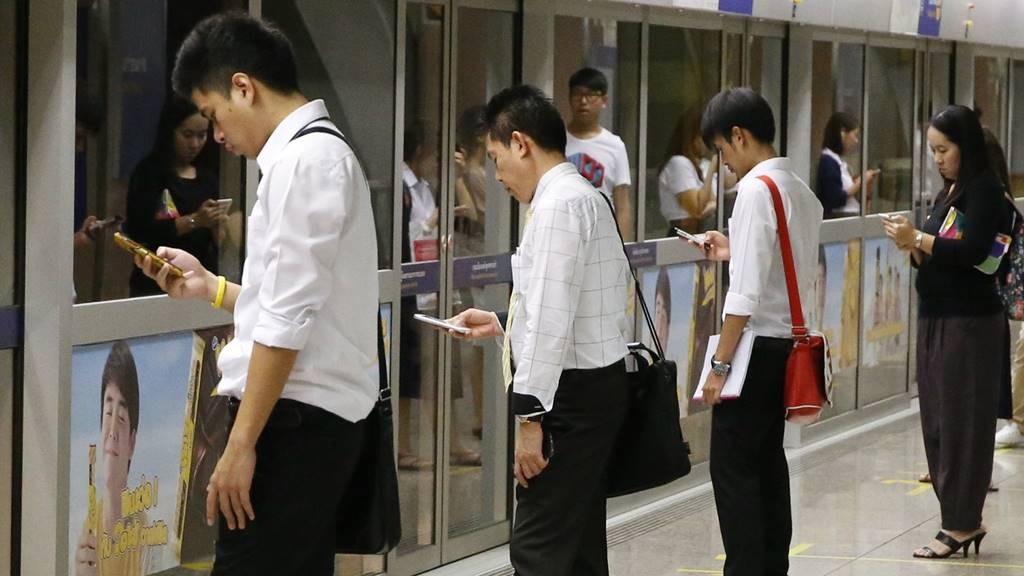 쿼츠 기사에 인용된 전철에서 스마트폰을 보면서 기다리는 사람들