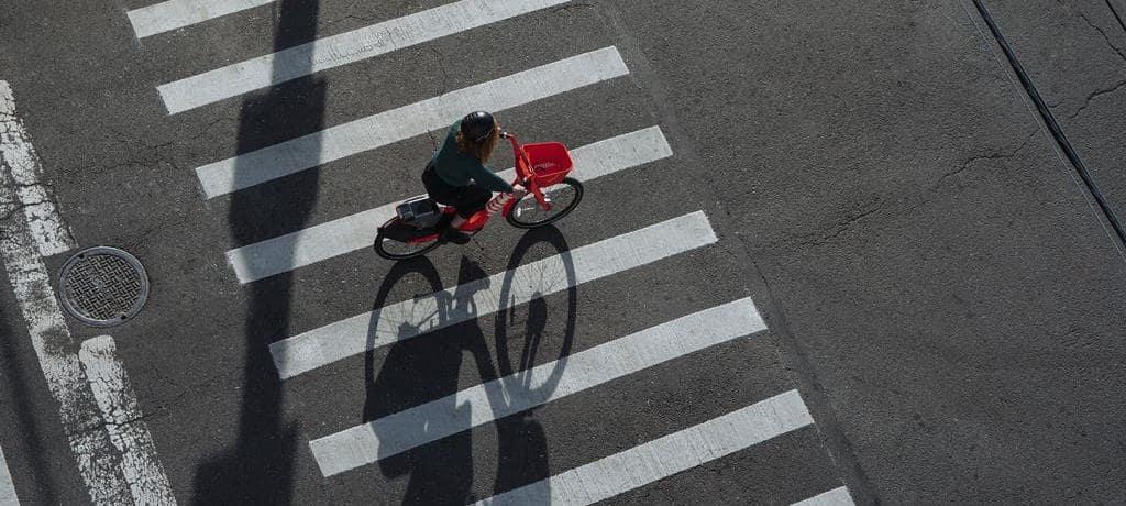 공유 자전거를 타고 건널목을 가로지르는 여자, Image - JUMP Bikes