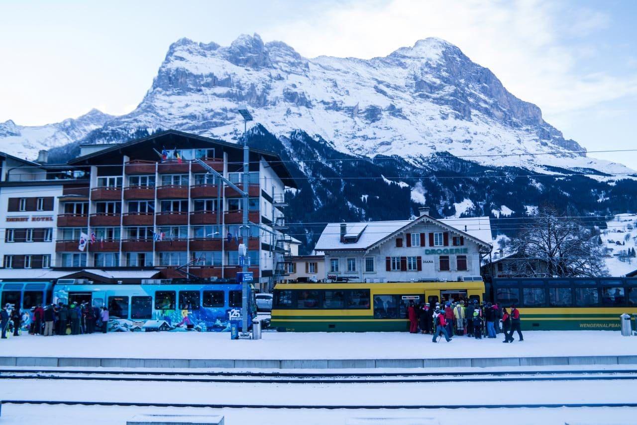 아이거산과 클라이네 샤이덱(Kleine Scheidegg)으로 가는 스키어들 그리고 알록달록한 열차들