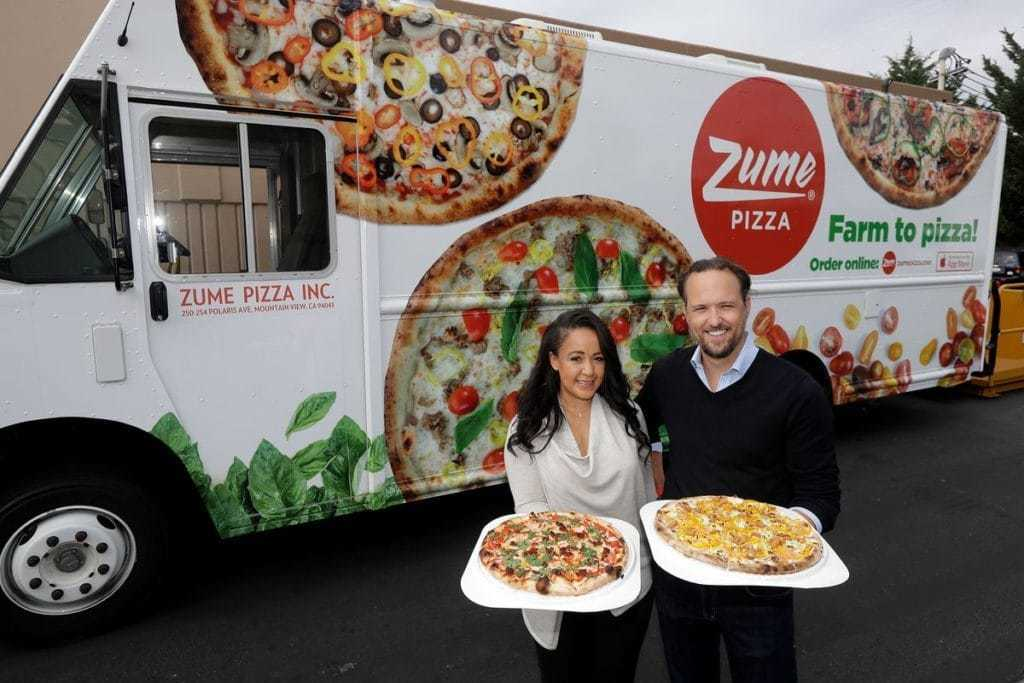 Zume 공동 창립자 Julia Collins와 Alex Garden가 회사 배달 트럭 앞에서 완제품 피자를 선보이고 있는 모습, Photo by MARCIO JOSE SANCHEZ