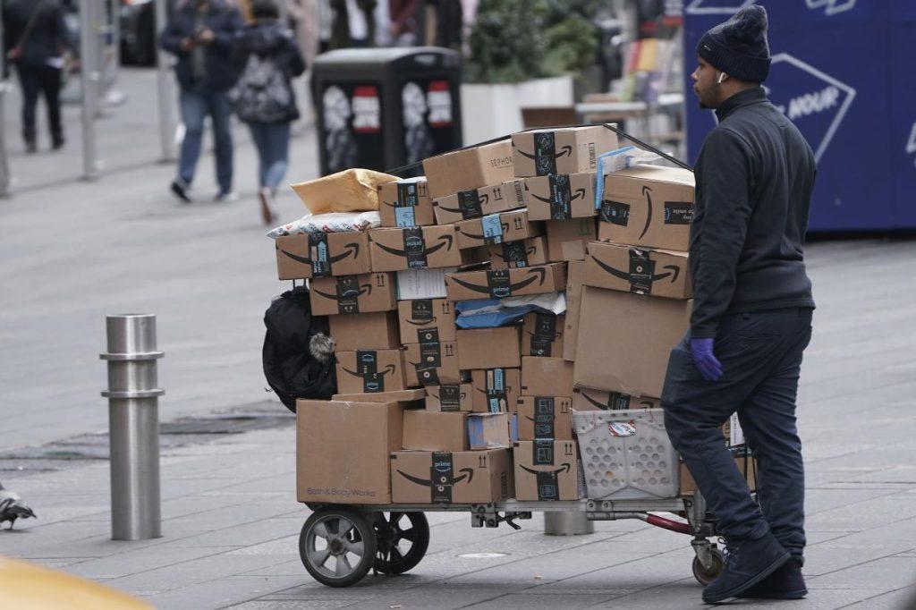 뉴욕 타임스퀘어의 아마존 택배 배달원, An Amazon delivery person walks in Times Square on March 17, Photo by REUTERS, CARLO ALLEGRI