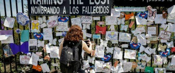 뉴욕 브루클린의 그린우드 공동묘지(The Green-Wood Cemetery) 외부에 게재된 코로나 사망자 추모 메모들과 이를 촬영하는 여인, Image from Reuters