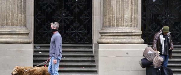 로스앤젤레스 할리우드 대로(Hollywood Boulevard in Los Angeles)에서 개와 산책하는 마스크를 쓴 한 남성이 노숙자를 지나치고 있는 모습, Photo by Richard Vogel, Associated Press