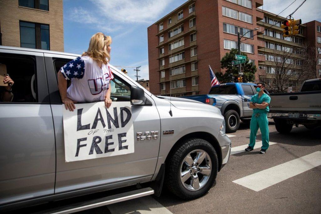 미국 콜로라도주에서 의료진으로 보이는 남성이 '외출금지령 해제'를 요구하는 시위대 행진을 막고 있다, Photo by ALYSON MCCLARAN