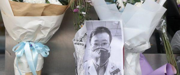 중국의 코로나19에 대한 미온적인 대처를 주장했던 우한 의사 Li Wenliang이 사망 후 우한 중앙병원 앞에 추모 사진과 꽃다발이 놓여져 있다. Photo by EPA-EFE, SCMP
