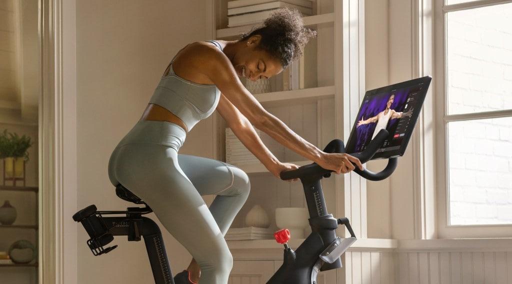 펠로톤 실내 사이클로 운동하는 여인, Woman with Peloton black bike product, Image from Peloton