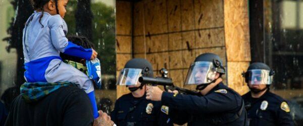 아이를 목마 태우고 있는 남자에게 총을 겨누는 미국 경찰, Photo by Richard Grand