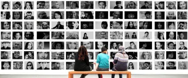 사람들 얼굴 사진이 가득한 벽 앞에 앉아 있는 사람들, human,Featured, Photo by geralt