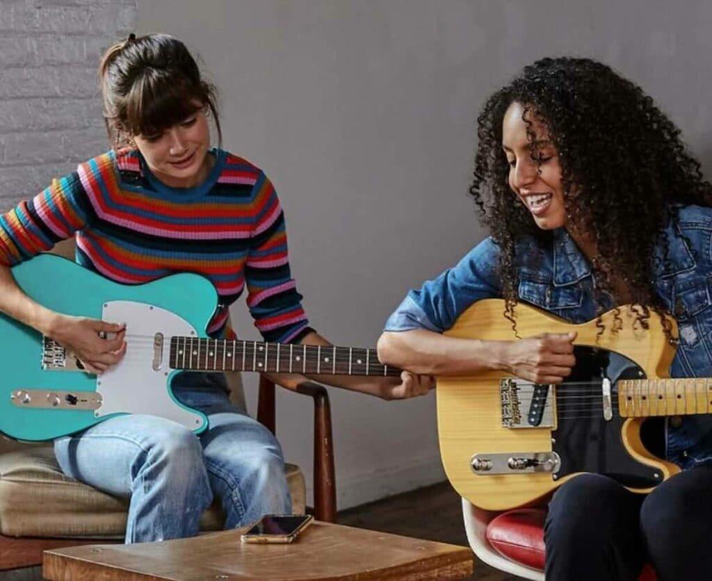스마트폰 텐더 플레이로 기타를 배우고 있는 두 여성, Image from Fender