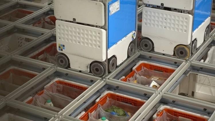오카도 풀필먼트 창고의 패키징 로봇들이 배송 바구니에 성품을 투하하고 있다